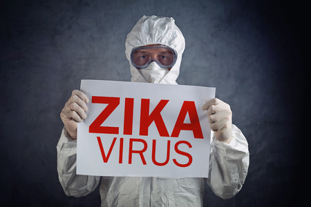 virus: Zika virus concept, medical worker in protective clothes showing alertness poster