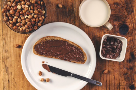 spread: Hazelnut nougat cream spread over bread slice, sweet delicacy for dinner.
