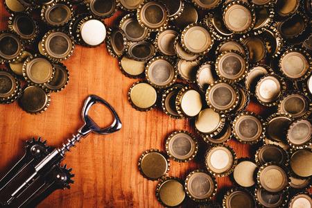 bottle opener: Classic bottle opener and pile of beer bottle caps on top of rustic oak wood desk, top view.