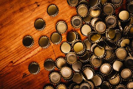 birretes: Las grandes montón de tapas de botellas de cerveza en la mesa de madera de roble rústico Foto de archivo