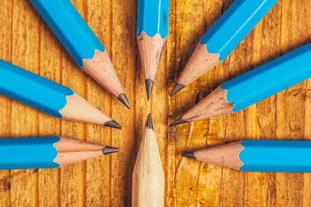 'odd one out': Standing out from the crowd, being different concept, surrounded by adversity, judging the odd one, wood pencils on desk Stock Photo