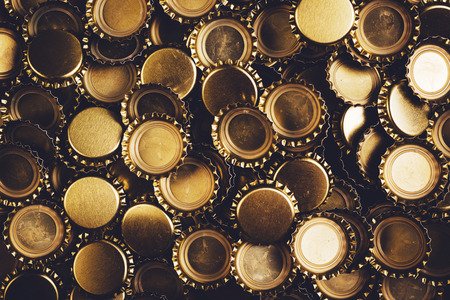 unbranded: Beer bottle caps heap, unbranded metallic caps as pattern background. Stock Photo