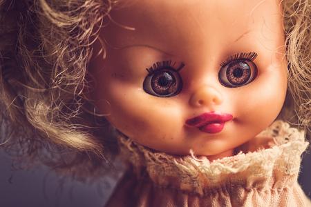 disturbing: Spooky vintage doll portrait, high contrast, retro toned image.