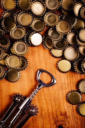 birretes: abridor de botella clásica y la pila de tapas de botellas de cerveza en la parte superior de la rústica mesa de madera de roble, vista desde arriba.