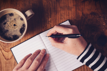 writes: Woman drinking coffee and making a diary note, top view of female hands writing in notebook, retro toned image with selective focus.