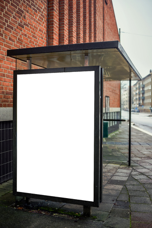 stop: Blank bus stop advertising billboard on empty street as copy space for outdoor poster ad mock up. Stock Photo