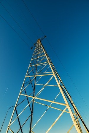 three phase: Transmission tower, high voltage electricity pylon with wires against blue afternoon sky, low wide angle view