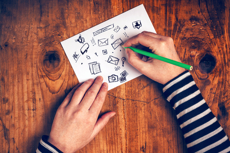 Female graphic designer sketching software icons on paper, top view, retro toned.
