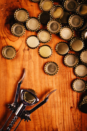 birretes: Classic bottle opener and pile of beer bottle caps on top of rustic oak wood desk, top view.