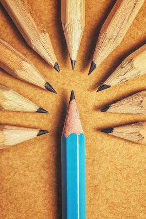 judging: Contempt toward unique ones, being different, weird, surrounded by adversity, judging the odd one, wood pencils on desk