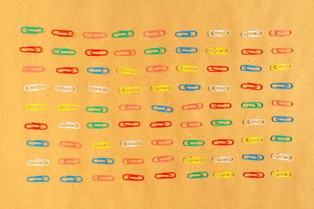 paper clips: Flat lay colorful paper clips arrangement on kraft paper background, office supplies top view.