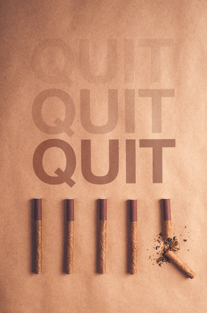 quit smoking: Quit smoking concept, flat lay arranged cigarettes with broken one at the end as final decision to quit is made, warm retro image tone. Stock Photo