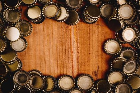 Beer bottle caps forming frame over oak wood plank as copy space.