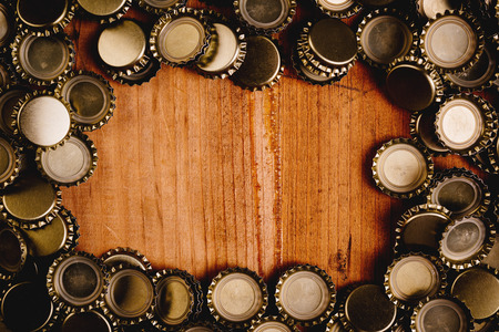Beer bottle caps forming frame over oak wood plank as copy space.