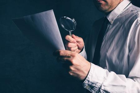 Belastinginspecteur het doen van financiële controle, zakenman het lezen van zakelijke rapport of contract voetnoten disclaimer met vergrootglas, retro afgezwakt, selectieve aandacht