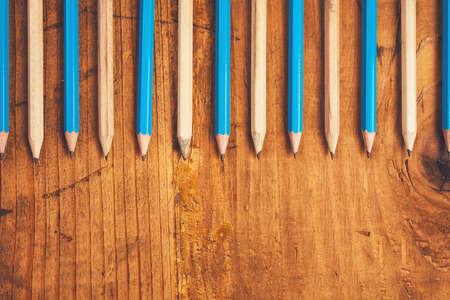 grafito: Blue and brown lined up pencils on rustic wooden table, top view with blank copy space Foto de archivo