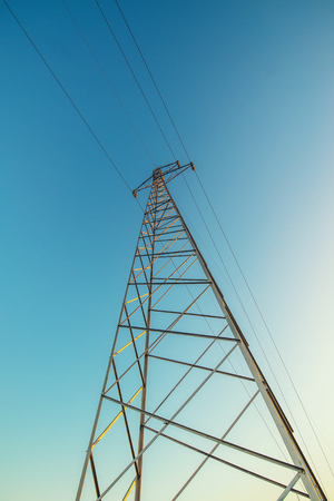 Transmission tower, high voltage electricity pylon with wires against blue afternoon sky, low wide angle view