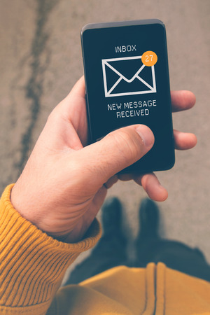 incoming: Using mobile smartphone to access e-mail inbox, man viewing incoming messages while walking on street, top view, selective focus, retro tone filtered image. Stock Photo