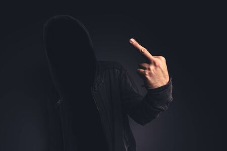 offensive: Middle finger offensive hand gesture given by unrecognizable hooded person. Stock Photo