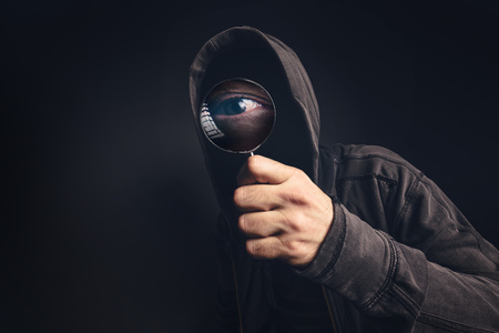 snoop: Bizarre hooded spooky person with magnifying glass, focus on enlarged eye peeking at you