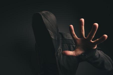 Portret van spooky hooded onherkenbaar persoon zonder gezicht in een donkere kamer