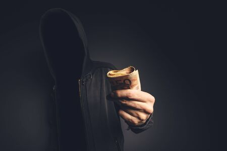blackmail: Unrecognizable hooded computer hacker offering cash money, cyber crime, blackmail and extortion concept.