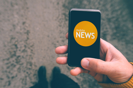 announcements: Mobile news reading on smartphone, man on the street using smart phone to read the latest news and announcements, top view, selective focus, retro tone filtered image.