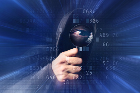 computer hacker: Spyware virus software, bizzare spooky hooded hacker with magnifying glass analyzing computer hexadecimal code, stealing online identity, breaking into personal web accounts. Stock Photo