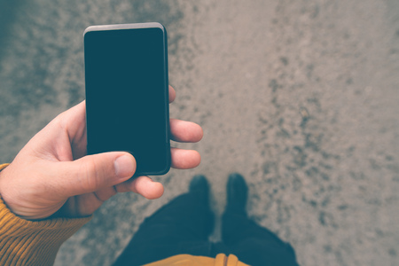 people in action: Using smartphone mobile on the street, text shuffle, man on the move holding mobile device in hand, screen as copy space, top view, selective focus, retro tone filtered image. Stock Photo