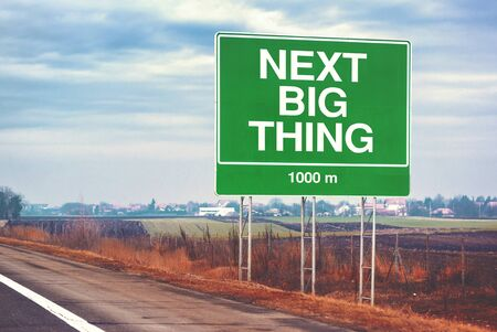 next: Next big thing ahead conceptual motivational image with road sign by the highway, retro toned image with selective focus