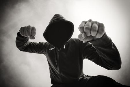 hombre fuerte: agresión calle, siendo golpeado y asaltado por el hombre violento agresiva en la chaqueta con capucha en la calle, perspectiva Punto de vista de la víctima, imagen en blanco y negro monocromático.