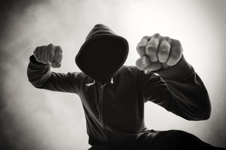 agression: Street agression, being punched and mugged by aggressive violent man in hooded jacket on street, victims pov perspective, monochromatic black and white image.