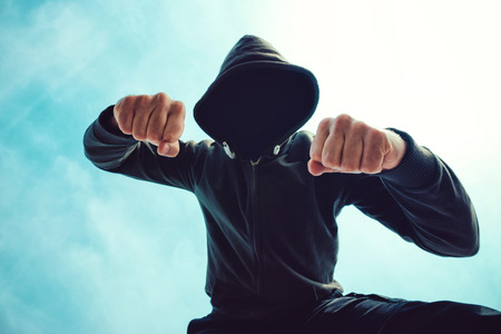 mugged: Being punched and mugged by aggressive violent man in hooded jacket on street, victims pov perspective.