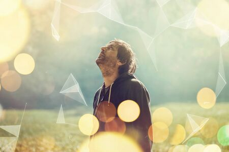 overlaying: Jogger resting after jogging in the park, standing and looking up to sky, futuristic shaped graphics overlaying image, retro toned image with selective focus and bokeh light Stock Photo