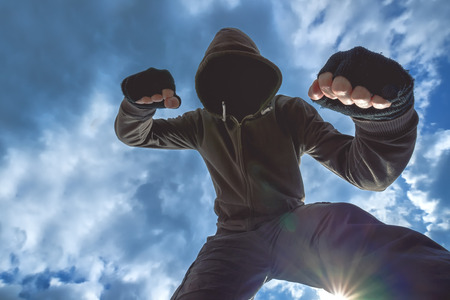 felon: Violent attack, unrecognizable hooded male criminal kicking and punching victim on the street. Stock Photo