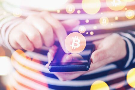 over paying: Woman paying with Bitcoins over smartphone, close up of female hands using mobile phone device to complete online shopping transaction, nice bokeh, close up with selective focus and shallow depth of field.