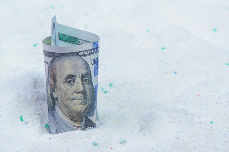 Saving money on quality cost-effective washing powder, dollar banknotes in laundry detergent.