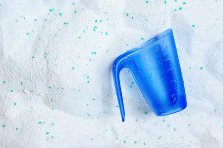 Wassen wasmiddel poeder en blauwe plastic maatbeker, bovenaanzicht