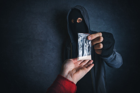 drug: Drug dealer offering narcotic substance to addict on the street, unrecognizable hooded criminal selling drugs in dark alley.