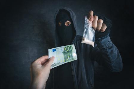 street drug: Drug dealer offering narcotic substance to addict on the street, unrecognizable hooded criminal selling drugs in dark alley for euro banknotes