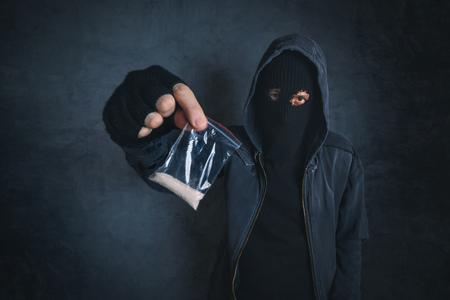 Drugsdealer aanbieden van verdovende substantie aan verslaafde op straat, onherkenbaar hooded criminele selling drugs in donker steegje, verslaafd persoon punt beeld De mening van de Stockfoto