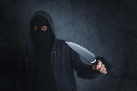 disturbing: Criminal with sharp knife threatening, victims point of view, disturbing violent scene of threatening terrorist in dark alley.