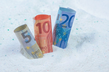 money and saving: Saving money on quality cost-effective washing powder, euro banknotes in laundry detergent.