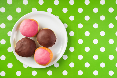 polka dotted: Top view of homemade tasty donuts with sweet strawberry and chocolate topping on a plate over polka dotted surface. Stock Photo