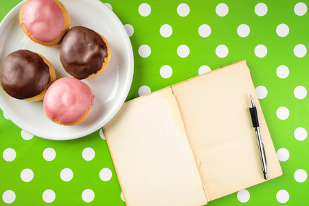polka dotted: Vintage notebook with recipe for delicious homemade donuts with topping, top view of cookbook with blank pages as copy space and tasty doughnuts on a plate over polka dotted surface.