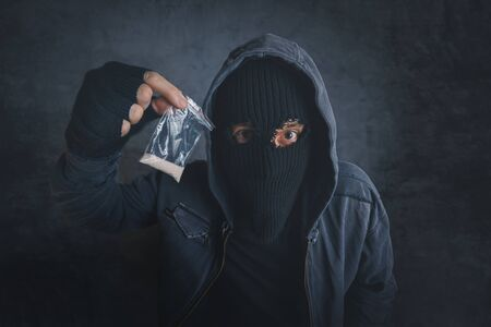 narcotics: Drug dealer offering narcotic substance to addict on the street, unrecognizable hooded criminal selling drugs in dark alley, addicted person point of view image