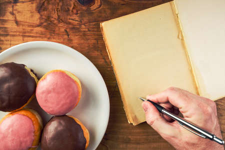 polka dotted: Writing recipe for homemade delicious doughnuts with sweet topping, top view of male hand writing in notebook and tasty donuts with sweet strawberry and chocolate topping on a plate over polka dotted surface. Stock Photo