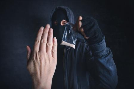 Saying No to drug dealer offering narcotic substance, fight addiction, unrecognizable hooded criminal offering drugs in dark street.