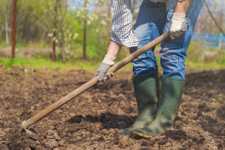 Man hoeing vegetable garden soil, new growth season on organic farm. Archivio Fotografico