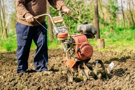 cultivator: Man preparing garden soil with cultivator tiller, new seeding season on home vegetable farm